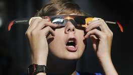 In this Wednesday, Aug. 16, 2017 photo, Colton Hammer tries out his new eclipse glasses he just bought from the Clark Planetarium in Salt Lake City in preparation for the eclipse. (Scott G Winterton/The Deseret News via AP)