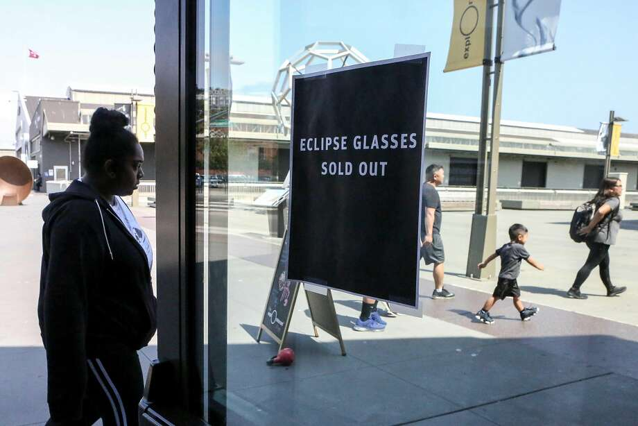 A sign posted on the front door says that all eclipse glasses are sold out as of Thursday at 1pm, at the Exploratorium science museum gift store in San Francisco. Photo: Amy Osborne, Special To The Chronicle