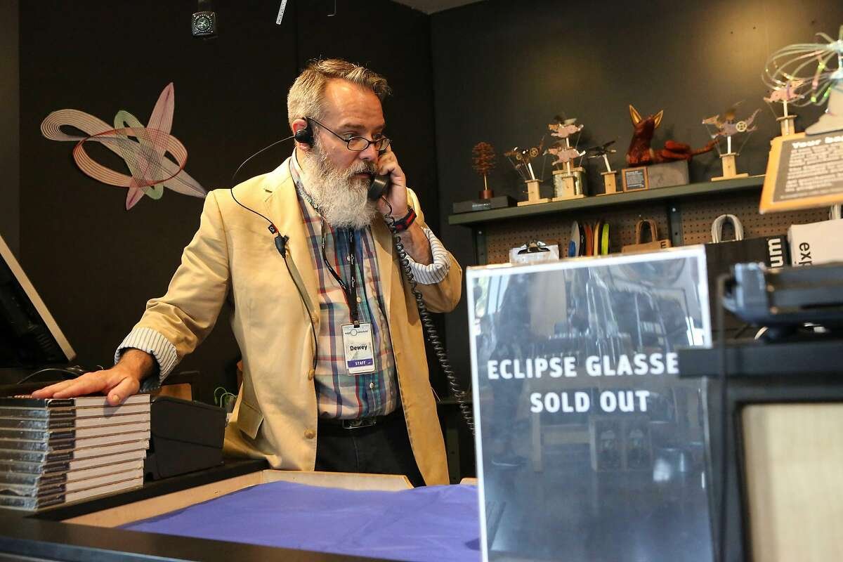 Exploratorium Museum gift store employee Dewey Bunger answers one of many phone calls asking if the store has any eclipse glasses left, on August 18, 2017 in San Francisco.