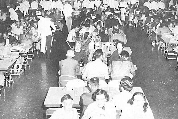 An early Rotary Club of Conroe Pancake Supper with the club members wearing white hats and serving the public. The event was the club's major fundraiser and was a tradition in Conroe for many years.
