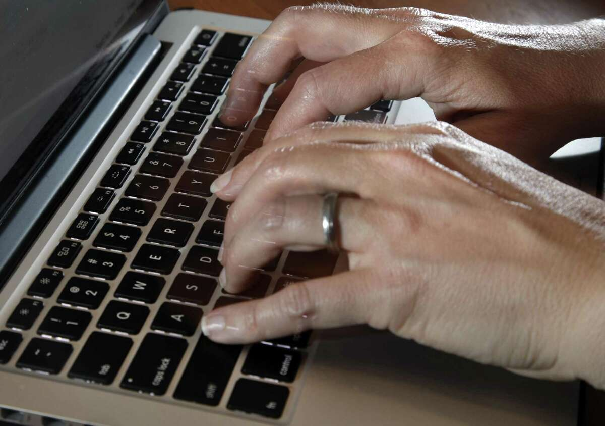In this Monday, June 19, 2017, photo, a person types on a laptop keyboard, in North Andover, Mass. The American workplace is grueling, stressful and surprisingly hostile. So finds an in-depth study of 3,066 U.S. workers, released Monday, Aug. 14, 2017, by the Rand Corp., Harvard Medical School and the University of California, Los Angeles.