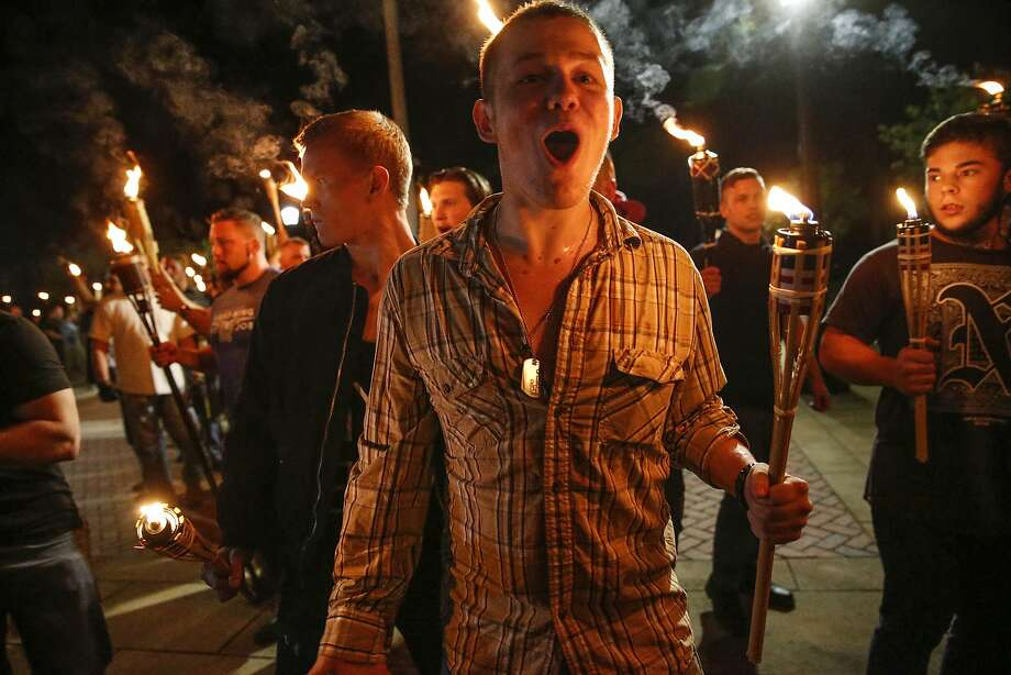 In this photo taken Friday, Aug. 11, 2017, multiple white nationalist groups march with torches through the UVA campus in Charlottesville, Va.   Hundreds of people chanted, threw punches, hurled water bottles and unleashed chemical sprays on each other Saturday after violence erupted at a white nationalist rally in Virginia.  (Mykal McEldowney/The Indianapolis Star via AP) Photo: Mykal McEldowney, Associated Press