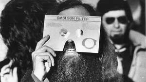 People watch as the moon eclipses the sun in the last total solar eclipse, Feb. 26, 1979.