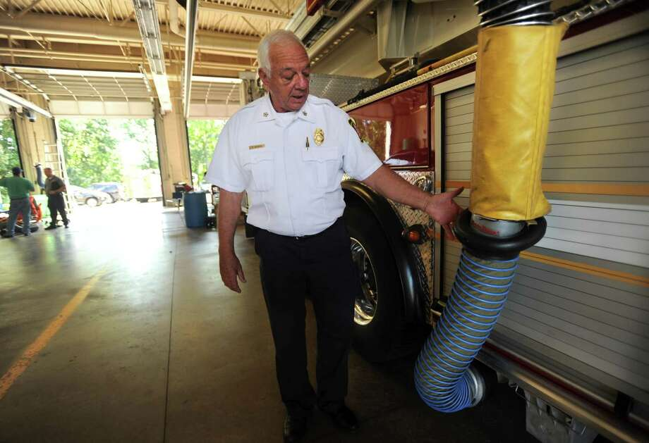 Stratford Fire Chief Robert McGrath shows the diesel particulate extraction system incorporated into each of the town's firehouses to remove diesel exhaust from the buildings at Stratford Fire Headquarters in Stratford, Conn. on Thursday, August 17, 2017. The system fits over each truck's exhaust pipe and attaches to the trucks magnetically. Photo: Brian A. Pounds / Hearst Connecticut Media / Connecticut Post