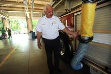 Stratford Fire Chief Robert McGrath shows the diesel particulate extraction system incorporated into each of the town's firehouses to remove diesel exhaust from the buildings at Stratford Fire Headquarters in Stratford, Conn. on Thursday, August 17, 2017. The system fits over each truck's exhaust pipe and attaches to the trucks magnetically.