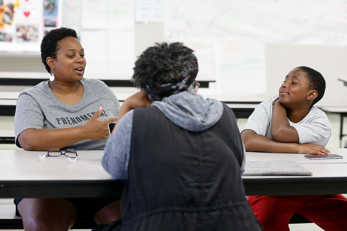 Founding parent Che Abram (left) and her son Naasir Abrim (right), 11 years old, are part of the design team for the new middle school called School of Language (SOL) with a dual immersion Spanish language program as they speak with Angie Noel in the cafeteria on Thursday, August 17, 2017, in Oakland, Calif..