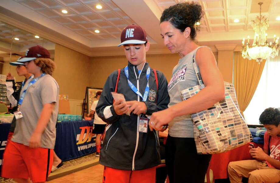 Fairfield American Anthony Pollack shows his mom Millie some little league pins he got for his collection while at Genetti's Hotel in downtown Williamsport, Penn., on Friday Aug. 18, 2017. Due to rain, team practice was cancelled, which allowed the kids to join their parents at the hotel. Photo: Christian Abraham / Hearst Connecticut Media / Connecticut Post