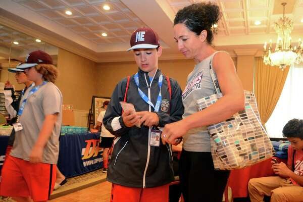 Fairfield American Anthony Pollack shows his mom Millie some little league pins he got for his collection while at Genetti's Hotel in downtown Williamsport, Penn., on Friday Aug. 18, 2017. Due to rain, team practice was cancelled, which allowed the kids to join their parents at the hotel.