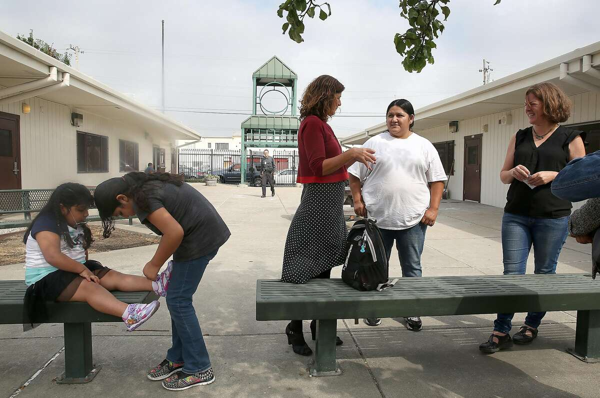 Oakland Community Organization's parent leader Katy Nu�ez-Adler (middle) and founding principal Katherine Carter (right in black shirt) talk with parents s at the School of Language (SOL), on Thursday, August 17, 2017, in Oakland, Calif..