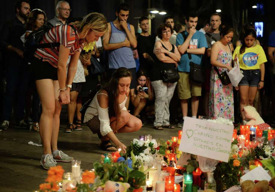 People at the Font de Canaletes in Barcelona pay tribute to the victims of  two attacks in Spain where 14 people were killed and more than 100 were injured. ISIS has claimed responsibility. Photo: JOSEP LAGO, Contributor / AFP or licensors