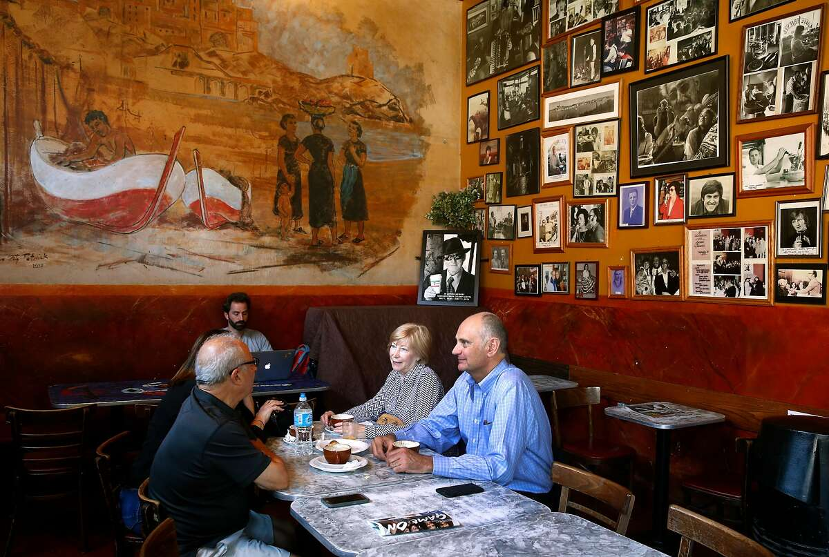 Patrons enjoy espresso drinks at Caffe Trieste below a mural and a wall of framed photos of famous previous guests of the North Beach institution, on Aug. 17, 2017.