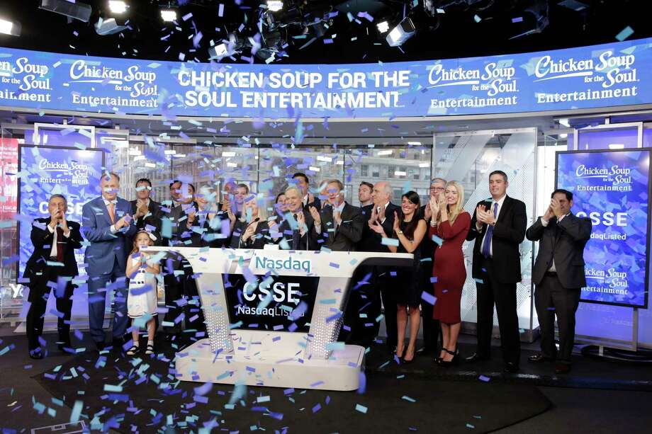 Chicken Soup for the Soul Entertainment Chairman & CEO William J. Rouhana Jr., center, rings the opening bell at the Nasdaq MarketSite to mark his company's IPO, in New York's Times Square, Friday, Aug. 18, 2017. With a total of 2,500,000 shares of Class A common stock sold at $12 per share, CSS Entertainment's offering is the largest exchange-listed IPO completed under Reg A& and the first to list on the higher tier Nasdaq Global Market. (AP Photo/Richard Drew) Photo: Richard Drew, STF / AP