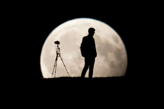 A man takes pictures of the moon standing in a partial lunar eclipse on August 7, 2017 in Munich, southern Germany. (Sven Hoppe/AFP/Getty Images)