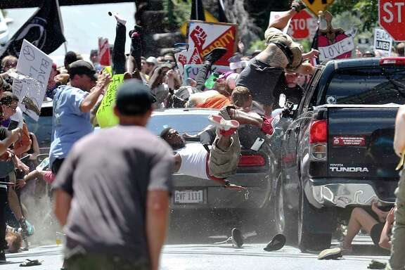 A vehicle drives into a group of protesters demonstrating against a white nationalist rally in Carlottesville, Va. A woman was killed, and at least 19 people were injured.  (Ryan M. Kelly/The Daily Progress via AP)