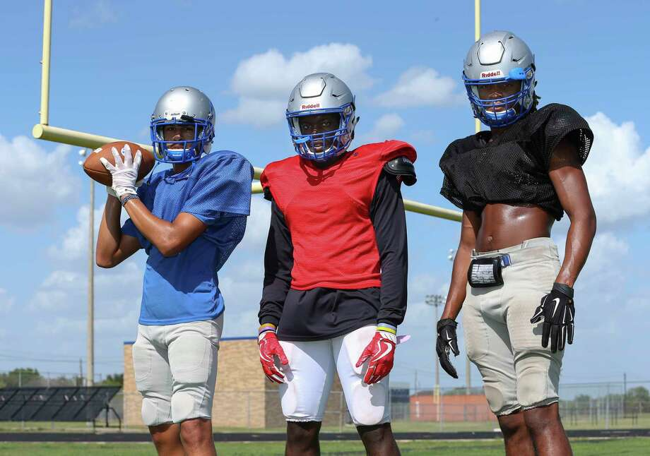 Willowridge High School football team players Vaughnte Frederick, 17, from left, Christian Carter, 16, and Daijuan Johnson, 18, pose for a photograph in their practice gear at the school field Thursday, Aug. 17, 2017, in Missouri City. Willowridge High School's building was contaminated with mold this summer, forcing the students to start the school year at rival high school, Marshall. ( Yi-Chin Lee / Houston Chronicle ) Photo: Yi-Chin Lee, Staff / © 2017  Houston Chronicle