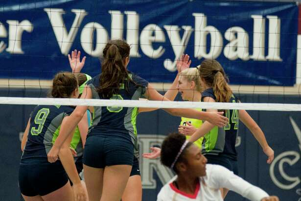 Members of the College Park volleyall team celebrate a point during a volleyball match between College Park and Cy Woods on Friday at College Park High School.
