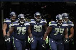 Seattle Seahawks' Germain Ifedi (76), Jarran Reed (90), and George Fant (74) take the field for warmups before an NFL football preseason game against the Minnesota Vikings, Friday, Aug. 18, 2017, in Seattle. (AP Photo/Stephen Brashear)