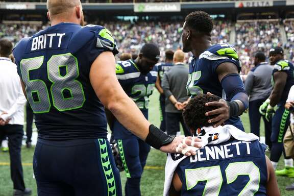 Seahawks center Justin Britt and cornerback Jeremy Lane place their hands on defensive end Michael Bennett sits for the playing of the national anthem before Seattle's preseason game versus the Minnesota Vikings on Aug. 18, 2017.