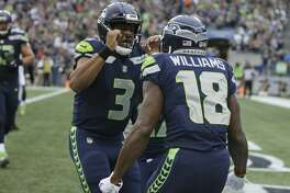 Seattle Seahawks wide receiver Kasen Williams (18) celebrates with quarterback Russell Wilson (3) after Williams caught a pass from Wilson for a touchdown in the first half of an NFL football preseason game against the Minnesota Vikings, Friday, Aug. 18, 2017, in Seattle. (AP Photo/Scott Eklund)