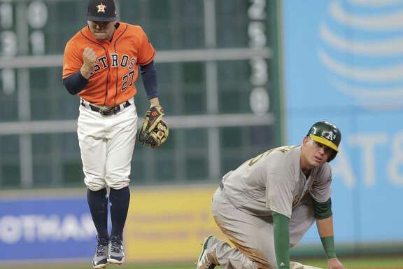 Astros second baseman Jose Altuve, left, celebrates after helping turn a double play against the Athletics on Friday night. The A's Ryon Healy was less than pleased about being doubled up on a ball hit by Chad Pinder.