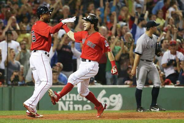 BOSTON, MA - AUGUST 18:  Tomy Kahnnle #48 of the New York Yankees looks on as Andrew Benintendi #16 and Eduardo Nunez #36 of the Boston Red Sox high five after scoring to take the lead in the seventh inning of a game at Fenway Park on August 18, 2017 in Boston, Massachusetts.  (Photo by Adam Glanzman/Getty Images) ORG XMIT: 700012079