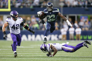 Seahawks running back Chris Carson leaps over Vikings corner back Jabari Price in the first half of a preseason game at CenturyLink Field on Friday, Aug. 18, 2017.