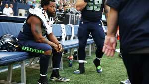 Michael Bennett sits on the bench for the second game in a row as the National Anthem is played before the Seahawks play the Minnesota Vikings in a preseason game, Friday, Aug. 18, 2017 at CenturyLink Field.