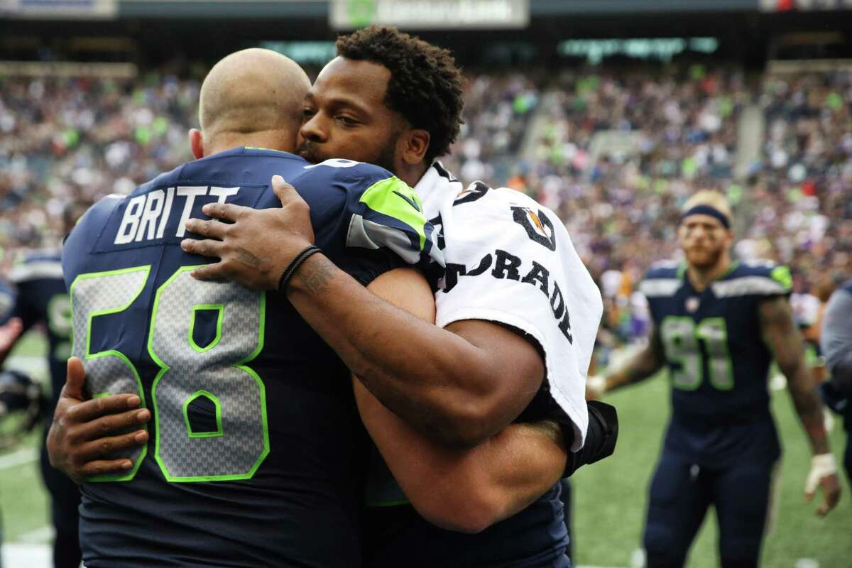 Justin Britt and Michael Bennett hug after Bennett sat on the bench for the second game in a row as the National Anthem played before the Seahawks game against the Minnesota Vikings in a preseason game, Friday, Aug. 18, 2017 at CenturyLink Field.