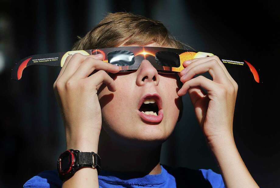 Here in Houston, onlookers will grab their solar eclipse shades (don't look directly at the sun without special protection) betweeen 11:50 a.m. and 3:02 p.m., according to NASA's Jet Propulsion Lab.  (Scott G Winterton/The Deseret News via AP) Photo: Scott G Winterton, MBO / ©Scott G Winterton/Deseret News 2017