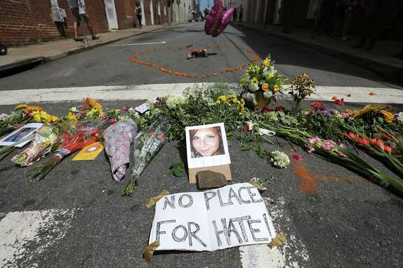 Flowers surround a photo of 32-year-old Heather Heyer, who was killed when a car plowed into a crowd of people protesting against the white supremacist Unite the Right rally in Charlottesville, Virginia.  (Photo by Chip Somodevilla/Getty Images)