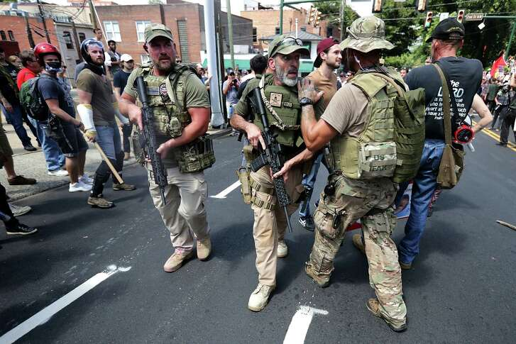 """White nationalists, neo-Nazis and members of the """"alt-right"""" with body armor and combat weapons evacuate comrades who were pepper sprayed after the """"Unite the Right"""" rally was delcared an unlawful gathering by Virginia State Police August 12, 2017 in Charlottesville, Virginia.  (Photo by Chip Somodevilla/Getty Images)"""