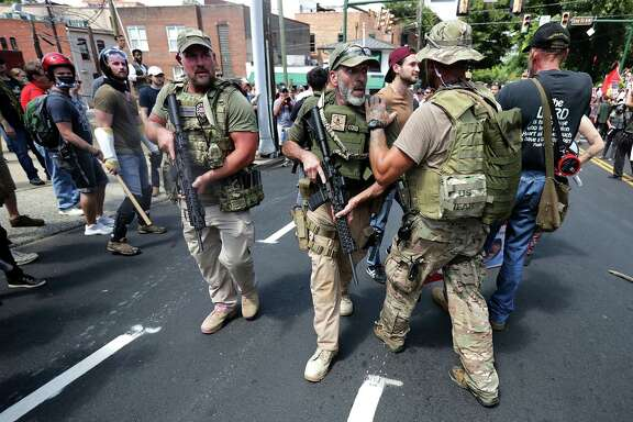 "White nationalists, neo-Nazis and members of the ""alt-right"" with body armor and combat weapons evacuate comrades who were pepper sprayed after the ""Unite the Right"" rally was delcared an unlawful gathering by Virginia State Police August 12, 2017 in Charlottesville, Virginia.  (Photo by Chip Somodevilla/Getty Images)"