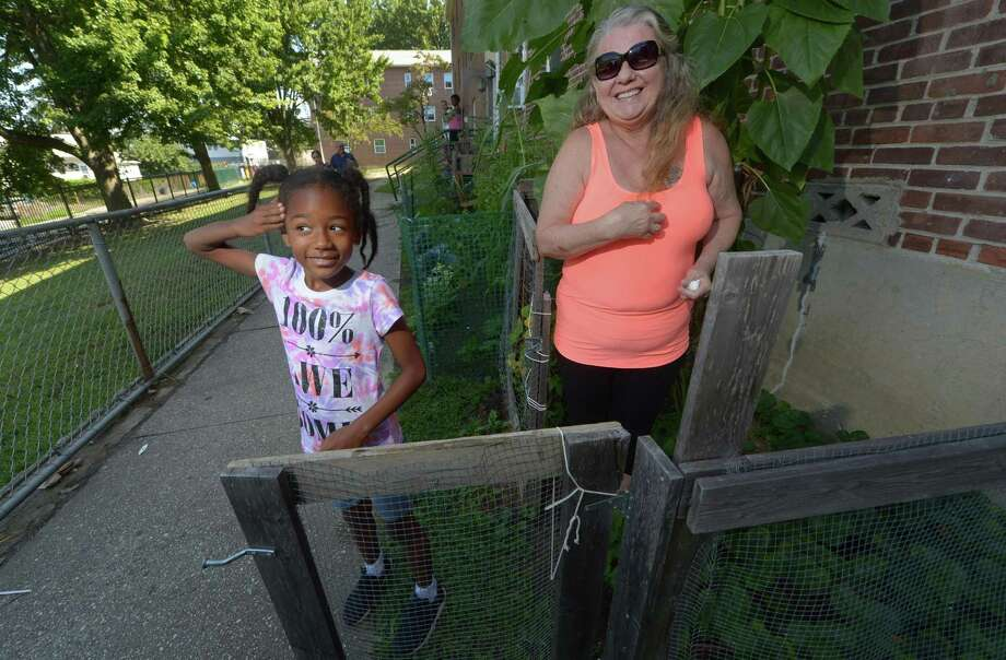 Roodner Court housing complex resident Debra George and her neighbor 8-year-old Yasley Dennison tend to the vegetable garden George started at the complex Wednesday, Aug. 16, in Norwalk. Photo: Erik Trautmann / Hearst Connecticut Media / Norwalk Hour