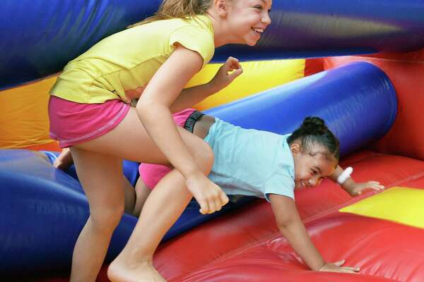 Jada Fitch, 9, left, and Ah'layah Splunge, 5, race through a bounce house at Epic Inc.'s Youth & Family Day at Jerry Burrell Park Saturday August 19, 2017 in Schenectady, NY.  (John Carl D'Annibale / Times Union)