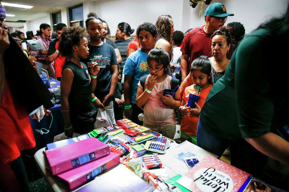 Students and parents pass by tables with giveaways and information at the Southside Takeover event at Worthing High School for schools participating in HISD's ACHIEVE 180 initiative Saturday, Aug. 19, 2017 in Houston. Photo: Michael Ciaglo, Houston Chronicle / Michael Ciaglo