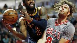 Cleveland Cavaliers guard Kyrie Irving looks to pass against Chicago Bulls center Robin Lopez during the first half on March 30, 2017, in Chicago.
