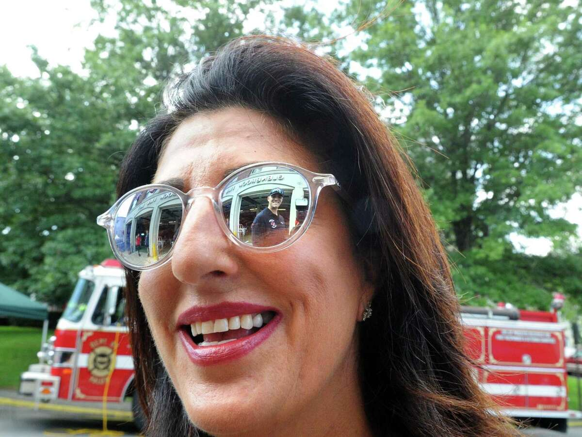 Glenbrook Fire Department Lt. Reema Odeh smiles as she speaks with fellow Glenbrook firefighter Sean Grogan (reflected in her sunglasses) during the Glenbrook Fire Department's 100th anniversary celebration at the station in the Glenbrook section of Stamford. Conn., Saturday, Aug. 19, 2017.