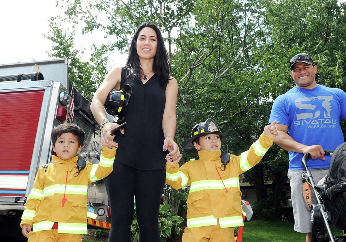 Lydia Schmidt of Stamford holds the hands of her son's Sivatau, 2, left, and Manusamoa, 4, who both wore firefighter outfits to the Glenbrook Fire Department's 100th anniversary celebration at the station in the Glenbrook section of Stamford. Conn., Saturday, Aug. 19, 2017. At right is Vincent Schmidt, Lydia's husband and the father of Sivatau and Manusamoa.