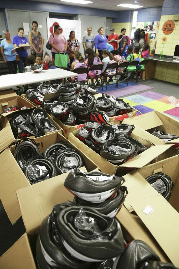 Boxes of helmets await as kids get backpacks and safety gear as well school supplies and vaccinations at the Garza Community Center back to school fair as on August 19, 2017. Photo: Tom Reel, Staff / San Antonio Express-News / 2017 SAN ANTONIO EXPRESS-NEWS