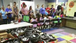 Boxes of helmets await as kids get backpacks and safety gear as well school supplies and vaccinations at the Garza Community Center back to school fair as on August 19, 2017.