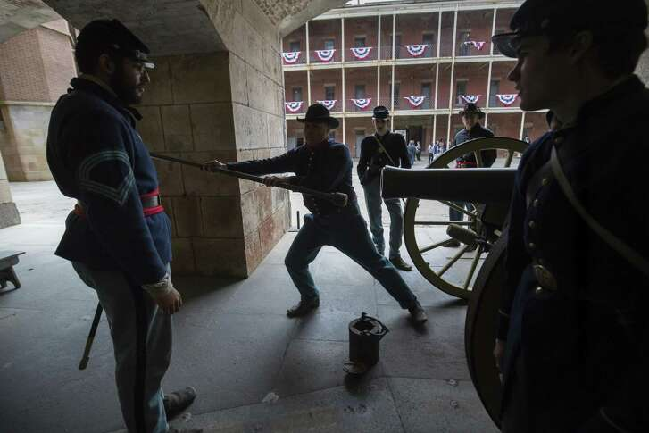 Re-enactors dressed in Union blue uniforms demonstrate how to fire a cannon during Civil War Living History Day at Fort Point in San Francisco.