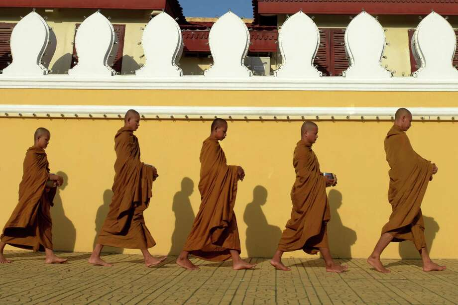 Buddhist monks walk in front of the Royal Palace in Phnom Penh, Cambodia. Photo: TANG CHHIN SOTHY, Contributor / AFP or licensors