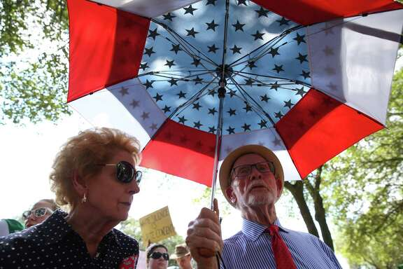 Two Black Lives Matter supporters brig out their American flag umbrella to protest Spirit of the Confederacy statue at Sam Houston Park on Saturday, August 19, in Houston.