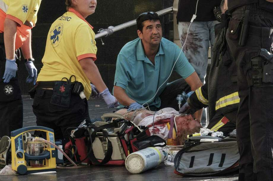 Paramedics tend to one of the many pedestrians struck by a van driving through crowds on Las Ramblas, Barcelona's most famous street, killing at least 12, on Aug. 17, 2017. At least 80 people were injured in what Spanish authorities described as a terrorist attack; two men have been arrested and the Islamic State group has already claimed responsibility. (Sergi Alcazar/El Nacional via The New York Times) -- NO SALES; FOR EDITORIAL USE ONLY WITH STORY SLUGGED BARCELONA-CRASH FOR AUG. 18, 2017. ALL OTHER USE PROHIBITED. — Photo: SERGI ALCAZAR/EL NACIONAL, STR / NYT / NYTNS