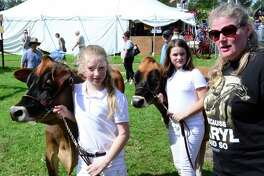 Becky Wheeler, 9, left, from Roxbury, Rebecka Klug, 9, from Torrington and Kris Wheeler from Roxbury wait for their turn in front of the judges for Two Best Female cows during the Bridgewater Country Fair on Saturday, August 19, 2017.