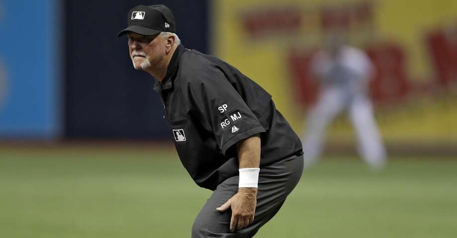First base umpire Dana DeMuth watches action between the Tampa Bay Rays and the Seattle Mariners during the first inning of a baseball game Saturday, Aug. 19, 2017, in St. Petersburg, Fla. The World Umpires Association, the union representing Major League Baseball umpires announced that umpires will be wearing white wristbands during all games to protest the escalating verbal attacks on umpires and their strong objection to the Office of the Commissioner's response to the verbal attacks. (AP Photo/Chris O'Meara) Photo: Chris O'Meara/Associated Press