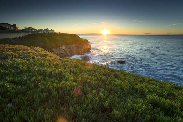 This is a high-angle shot showing the sea view of Monterey bey during sunrise. It also shows grass field, flower and a clif.
