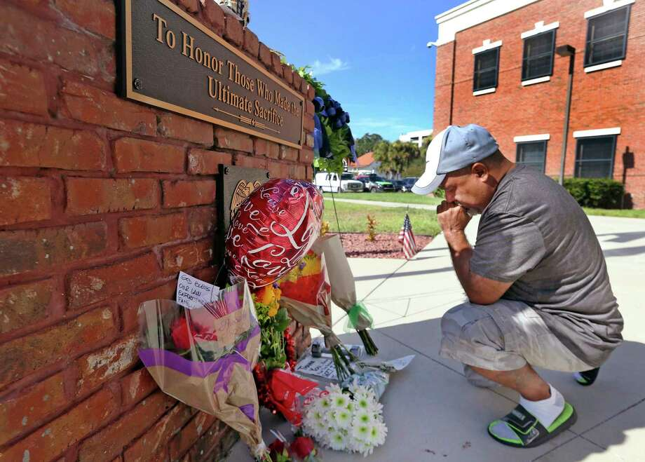 Miguel Velez prays at a makeshift memorial for the officer killed Friday in Kissimmee, Fla. A sergeant also was shot and died later of his wounds. Photo: Red Huber, MBO / Orlando Sentinel
