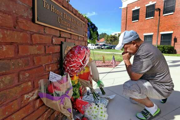 Miguel Velez prays at a makeshift memorial for the officer killed Friday in Kissimmee, Fla. A sergeant also was shot and died later of his wounds.