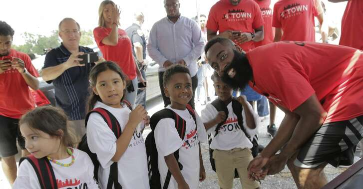 James Harden poses for a photo with some young recipients of  backpacks and school supplies on  Friday, Aug. 18, 2017, in Houston. ( Elizabeth Conley / Houston Chronicle )